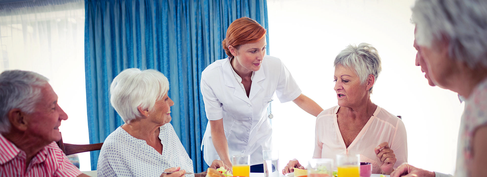 nurse and elderly group talking